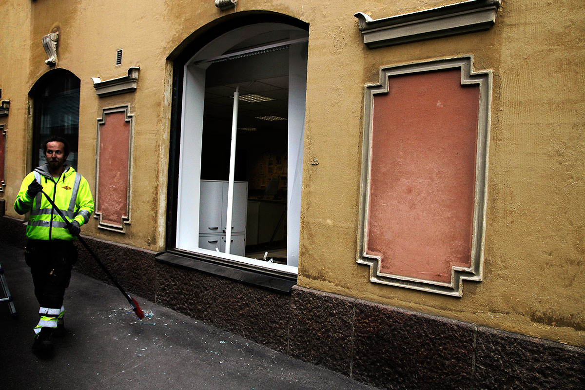 A man sweeping fragments of glass after a wild moose jumped through the window of Nordea bank at Museokatu near Helsinki center on May 26, 2016. Picture: Tony Öhberg for Finland Today