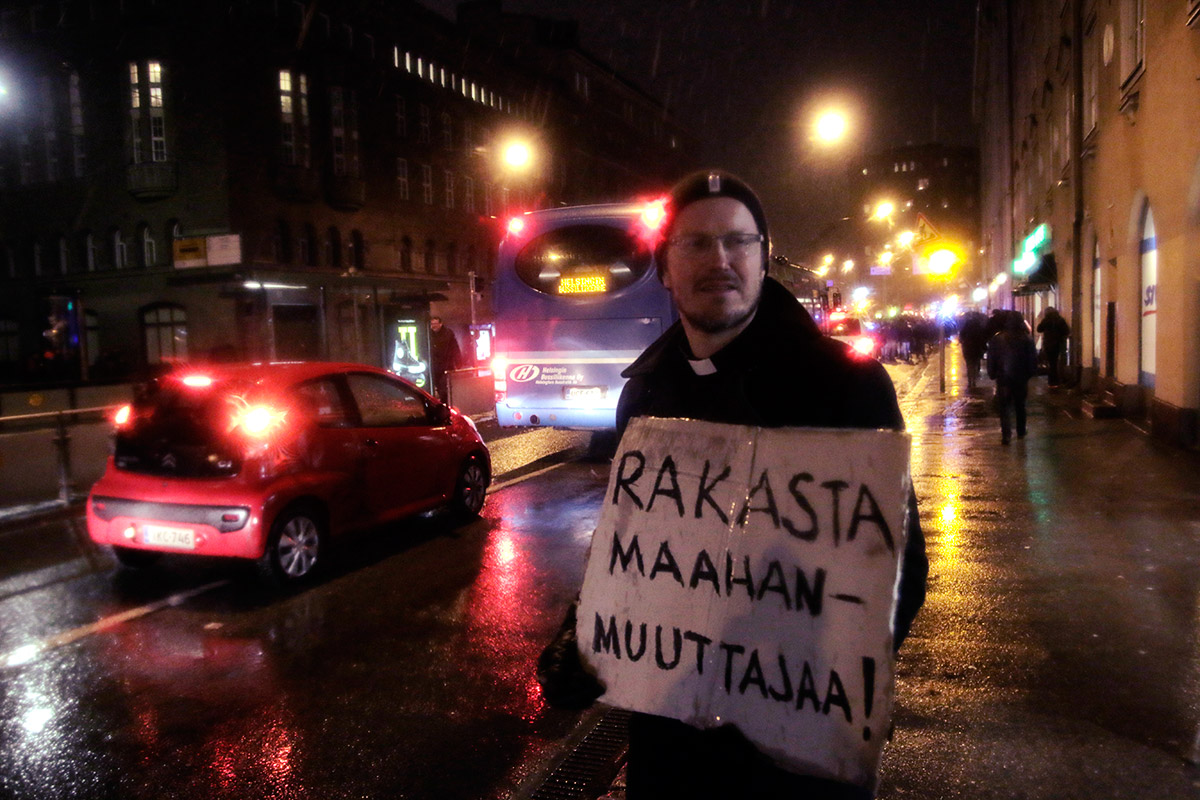 "A priest, Kai Sadinmaa, holding a sign saying ""Love an immigrant!"" Picture: Tony Öhberg for Finland Today"