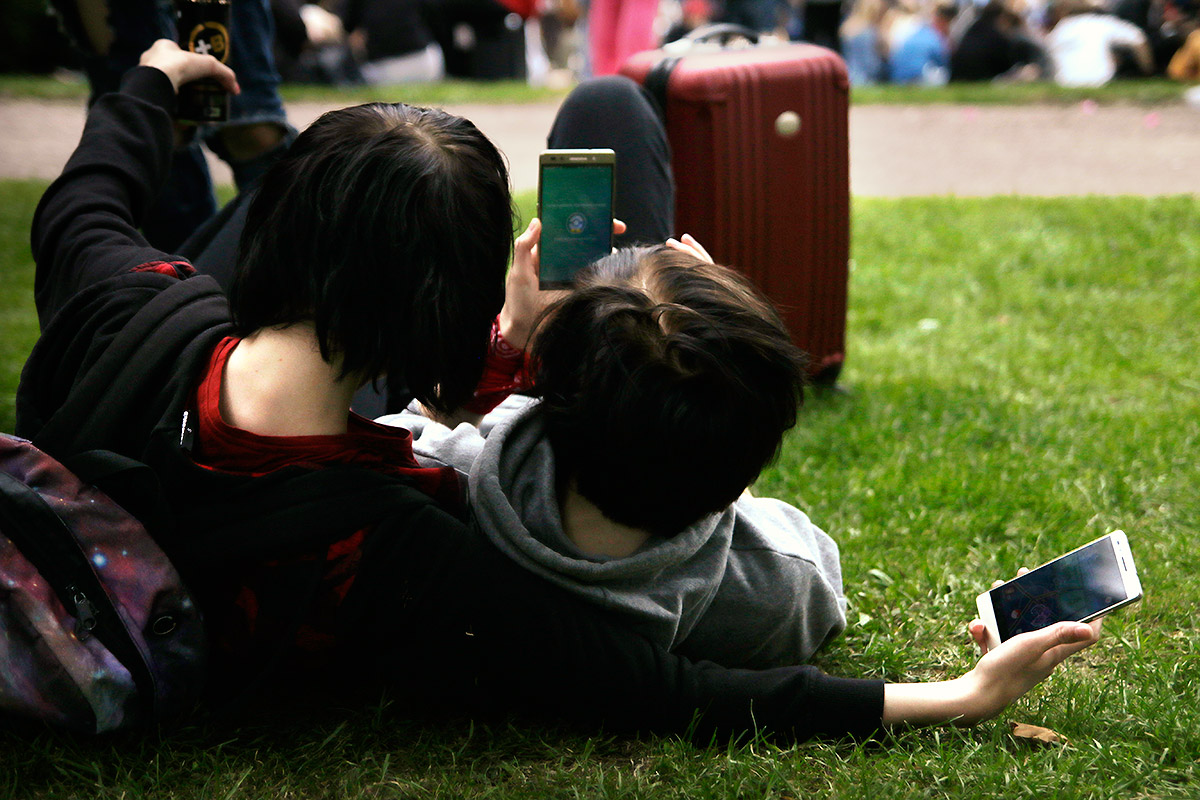 Pokémon Go players cuddling while playing the augmented reality game that has taken the world by storm at Kaisaniemi Park in Helsinki, Finland on July 22 2016. Picture: Tony Öhberg for Finland Today