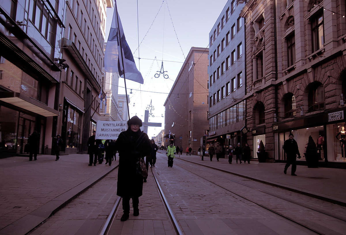 A woman flying the national flag at half-mast at Aleksanterinkatu in commemoration for the 14,500 entrepreneurs who committed suicide during the 90s depression in Finland. The procession, where a few dozen people attended, was arranged by a support group for debtors. Picture: Tony Öhberg for Finland Today