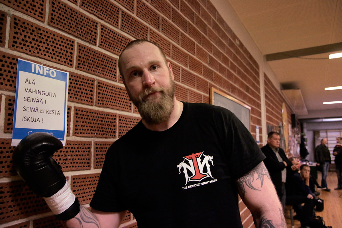 "Helenius standing next to a sign that says ""Do not damage the wall! The wall can't take punches!"" Picture: Tony Öhberg for Finland Today"