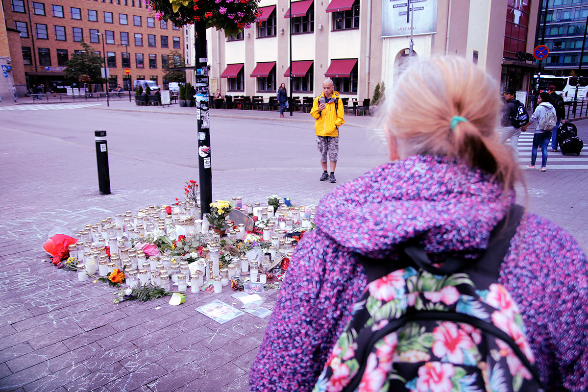Passers-by stopping at the memorial site. Picture: Tony Öhberg for Finland Today