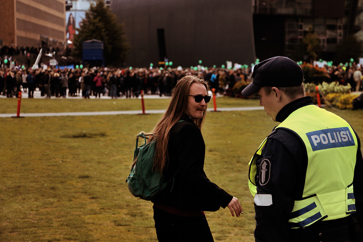 A man is being escorted to the other side after inviting the nationalists to join the protest against racism. Picture: Tony Öhberg for Finland